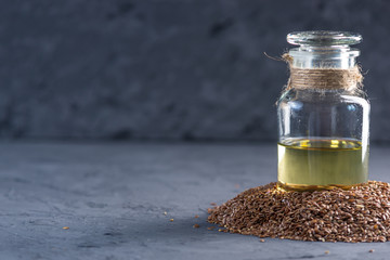 Flax seeds in a pile and linseed golden oil in a glass bottle on a dark background. Diet with omega 3 fatty acids.
