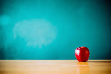 Apple on the desk in front of blackboard
