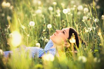 Summer scene. Girl in white dandelions enjoying evening time. Young woman relaxing outdoors.
