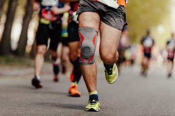 Wall Mural - foot runner man in knee pads running ahead of group marathon runners
