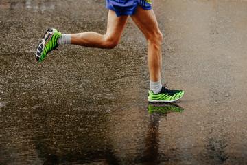 legs athlete runner running on wet from rain gray asphalt