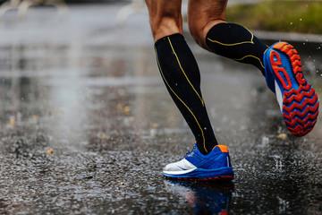 foot men runner in compression socks running on rain asphalt on water
