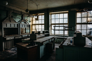 Abandoned creepy room of industrial building with old furniture, dramatic creepy scenery