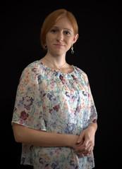 Rotblonde junge Frau mit geblümter Bluse
