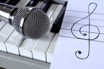 Synthesizer, microphone and treble clef on white paper