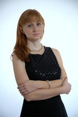 Rotblonde junge Frau im schwarzen Ballkleid
