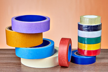 Multicolored rolls of insulation and masking tape lie on table.