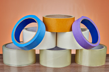 Pyramid of adhesive tape for various purposes, orange background.