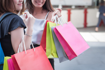 joyful, cheerful, smiling, happy girl shopper go shopping together with her best friend; portrait of women hand holding shopping bag, urban girls shopping concept; asian 20s young adult woman models
