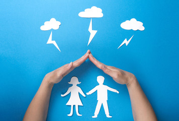 Life insurance and family health concept. Hands protect paper figures origami from lightning from the clouds on blue background. Man and woman holding hands under roof.