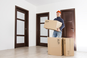 Mover with cardboard box at indoors of apartment. Relocation services man in hat holds boxes. Delivery man with parcel. Loader holding box.