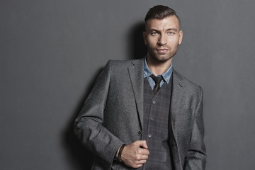 Portrait handsome fashionable man in suit against gray wall
