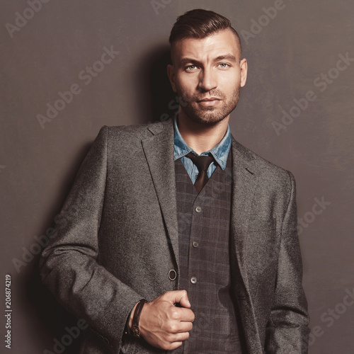 36a1aab4b8 Fashion model handsome stylish man in suit on gray wall background. Elegant  fashionable beautiful brutal