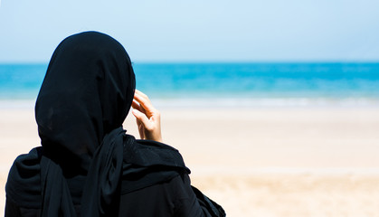 Muslim woman on the beach back view