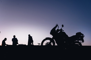 silhouette adventurous motorcycle on blue sunset sky with people, motorcyclists, motorcycle touring background, adventure and travel concept, active lifestyle
