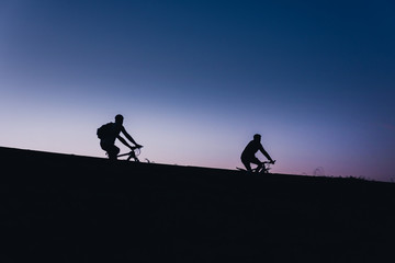 Beautiful Couple on bicycles silhouette sunset two bike ride
