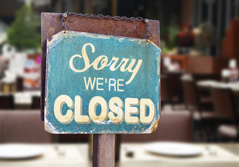 sorry we are closed sign hanging outside a restaurant, store, office or other