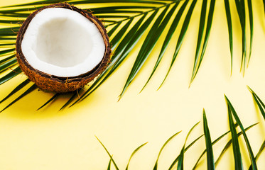 Coconut halves and leaves on yellow background