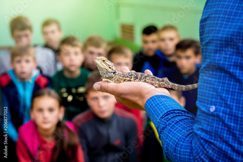 Wall mural Ukraine. Khmelnytsky region. May 2018. Man holds a gray lizard on his hand and shows it to children_