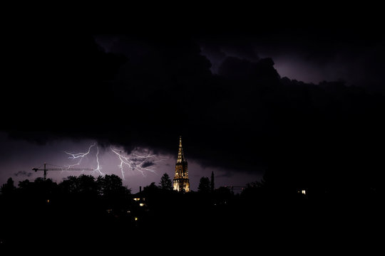 Lightning illuminates the sky above the Muenster Cathedral in Bern