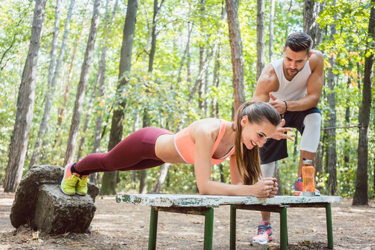 Beautiful woman doing a plank with man watching and cheering