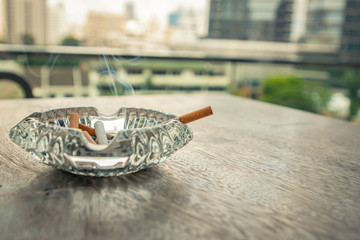 Smoking cigarette in ashtray on the wood table. Tree and City background. Retro and Vintage style.