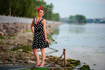 A beautiful young woman dressed standing by the lake, on the background of the sunset