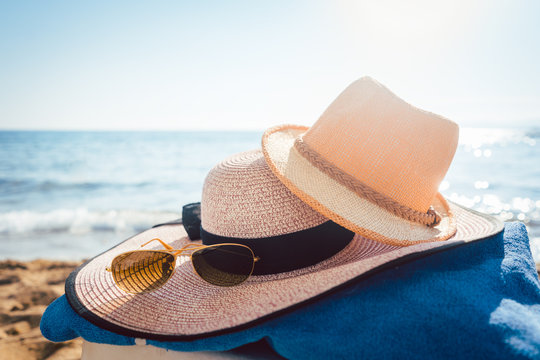 Sun hats and glasses on beach in the sand by the water