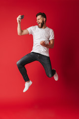Excited young man make selfie by mobile phone jumping.