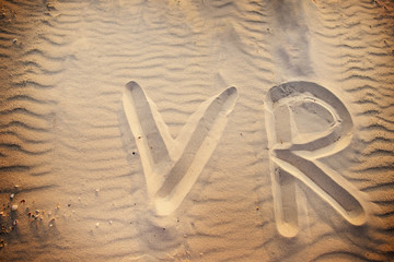The word VR is written on the sand on a wonderful sunny day