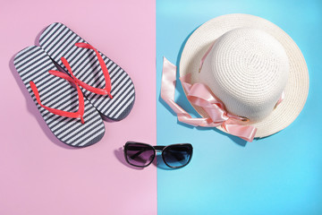 Beach accessories. Flip-flops and a summer hat with black sunglasses on a bright pink and blue background. Top view