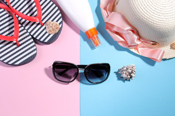 Beach accessories. Flip-flops and a summer hat with black sunglasses and cream on a bright pink and blue background. Top view