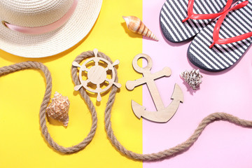 Marine paraphernalia and beach accessories. Wooden steering wheel and an anchor with a rope on a bright pink and yellow background. Top view.