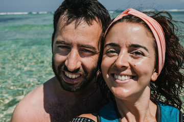 .Lovely couple on vacation in the gili islands enjoying at the lonely beach with turquoise blue water, relaxing and sunbathing. Travel photography.