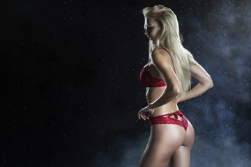 Beautiful wet sporty big tits tanned blonde girl wearing red underwear posing sideways ans from the back in scenic smoke and fog under falling water drops of rain on black
