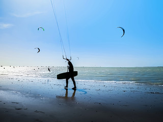 Kite surfer on the ocean beach. Silhouette of kite surfer across the sea shore.