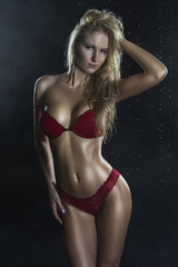 Beautiful wet sporty big tits tanned blonde girl wearing red underwear posing in scenic smoke and fog under falling water drops of rain on black.