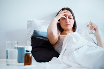 Ill woman feeling headache and lying in the bed