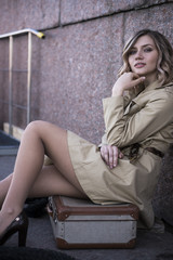 Attractive Young Blonde Woman in Trench sitting on Vintage Suitcase on the Jacht Pier