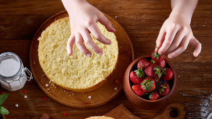 Top view of girl's hands decorating a cake with strawberries, close-up, selctive focus, vertical.