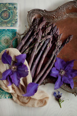 Fresh dark green, violet asparagus decorated on vintage plate with beautiful violet clematis flowers and turquoise oriental patterns, can be used as background