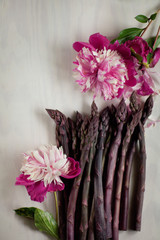 Fresh dark green, violet asparagus decorated on wood kitchen plate with beautiful peonies, can be used as background