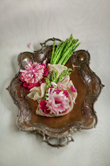 Fresh green asparagus decorated on a vintage metal plate on white wood kitchen plate with beautiful peonies, can be used as background