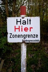 """Schild an der ehemaligen innerdeutschen Grenze mit der Aufschrift """"halt hier Zonengrenze"""""""