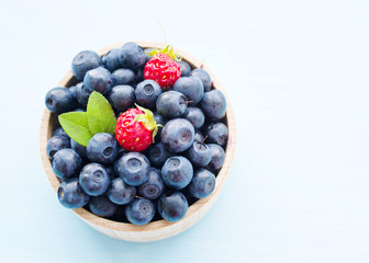 Fresh blueberries in a wooden cup on a light surface. Closeup, top view.