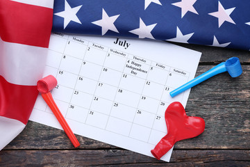American flag with paper July calendar and blowers on wooden table