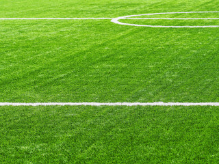 Green synthetic grass on sport ground with white lines. White stripe on the green soccer field from side view. Artificial turf on football field