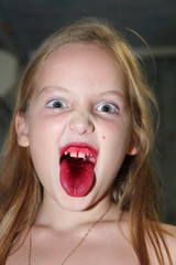 Emotional expression of the little girl's face with long hair showing her stained claret tongue from mouth