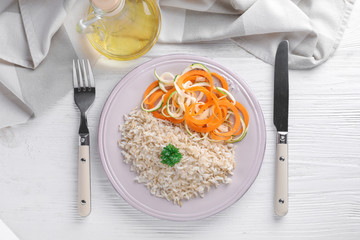 Plate with tasty brown rice and vegetables on table