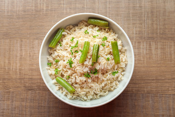 Bowl with brown rice and green beans on table
